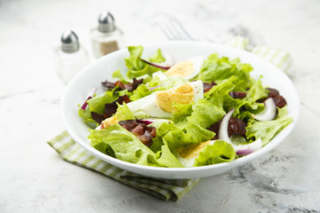 Lettuce salad with fried bacon, red onion and hard boiled egg