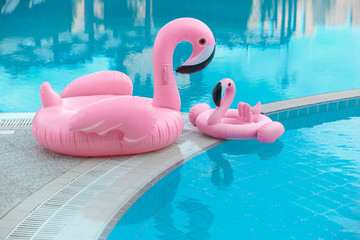 Foto op Canvas Flamingo Family look. Two Pink flamingo inflatable swimming pool ring, tube, float. Summer vacation holiday luxurious resort.