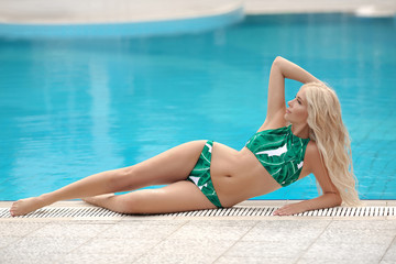 Sexy model in green leaves print bikini sunbathing by infinity swimming pool. Luxury travel vacation. Brunette Woman sunbathing at luxurious resort. Beautiful destinations concept.