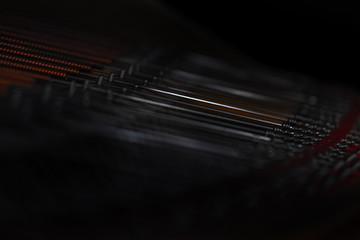 Close-Up von Konzertflügel-Saeiten  mit dunklem Hintergrund und viel Unschärfe