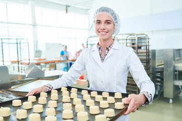 Confectioner in white uniform staying in factory with pastries and smiling looking at camera