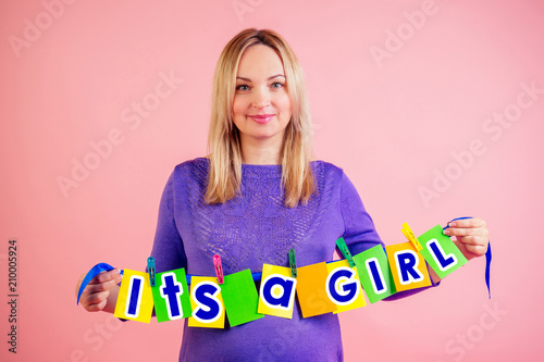 Beautiful Smiley Pregnant Big Belly Woman At 9 Months Of Pregnancy Hold A Cards With The Inscription Its Girl In Studio On Pink Background Waiting