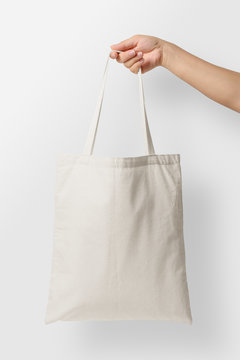Mockup of female hand holding a blank Tote Canvas Bag on light grey background. High resolution.