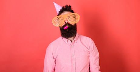 Man with beard on calm face with party horn, red background. Guy in party hat with holiday attributes celebrates. Surprise concept. Hipster in giant glasses blows into party horn