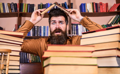 Deadline concept. Man on shocked face between piles of books, while studying in library, bookshelves on background. Teacher or student with beard sits at table making roof out of book, defocused.