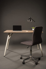 chair and table with lamp, plant, book and laptop with blank screen on grey background