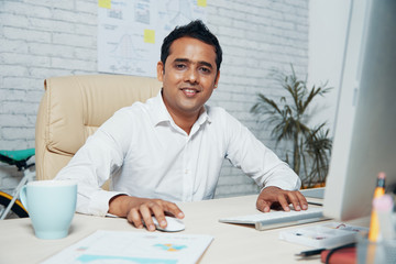 Handsome Indian businessman smiling at camera while working on computer at office