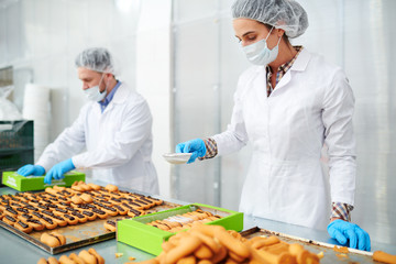 Confectionery factory worker in white coat sifting powdered sugar on ready pastry in box.
