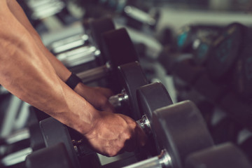 Close-up shot of sport man taking dumbbells from rack while having workout at modern gym