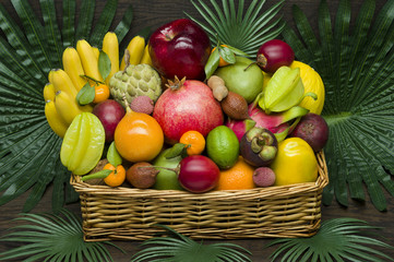 Photo Blinds Fruits Fresh Thai fruits in wicker basket on palm leaves and wooden background, healthy food, diet nutrition