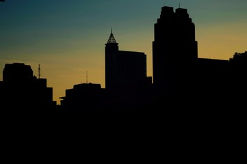 Silhouettes of the towers along the skyline of downtown Raleigh North Carolina just before sunrise on a clear morning