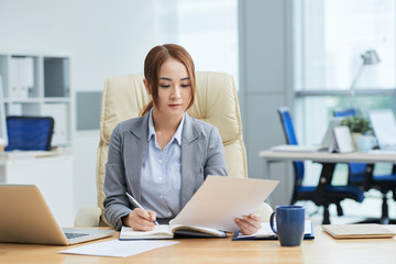 Asian young businesswoman working with documents at the table