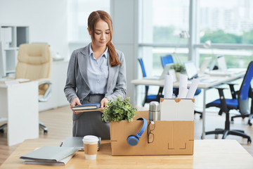 Businesswoman packing her stuff into the box at office