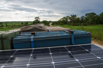 Roof of 4x4 offroad vehicle with jerry can, solar panel, roof top tent and storage box on dirt track in Angola, Africa