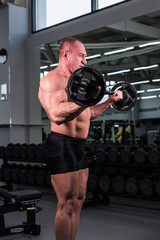 Handsome bodybuilder man with big muscles in the gym