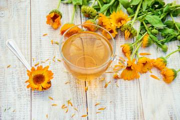 calendula tea and flowers. Selective focus.