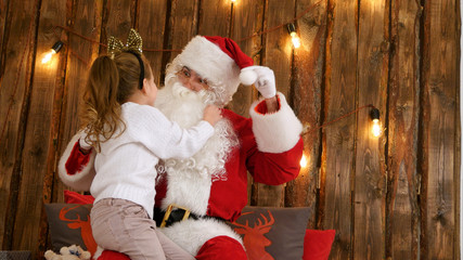 Cute little girl pulling Santa's beard to check if it's real sitting on his lap