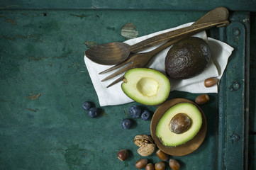 Cloth, salad cutlery, avocados, blueberries and nuts on green ground