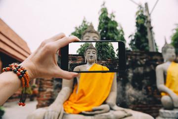 Thailand, Ayutthaya, Wat Yai Chai Mongkhon, taking a photo from Buddha with smartphone