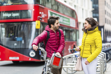 UK, London, young man with rental bicycle from bike share stand  talking to his girlfriend