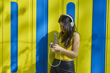 Young woman listening music with headphones and water bottle text messaging