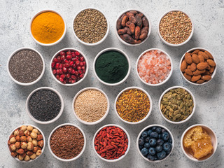 Various superfoods in smal bowl gray concrete background. Superfood as chia, spirulina, raw cocoa bean, goji, hemp, quinoa, bee pollen, black sesame, turmeric. Top view or flat-lay.