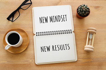 top view image of table with open notebook and the text new mindset new results. success and personal development concept.