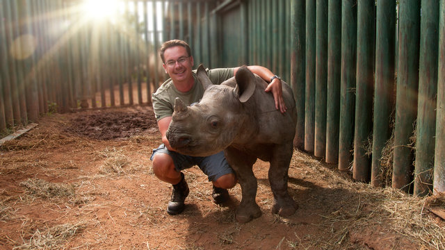 Mann mit Nashornbaby