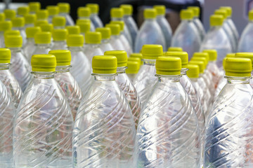 Group of plastic bottles with water stand in a row. Close-up