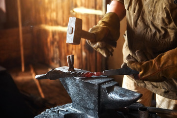 Blacksmith working on metal on anvil at forge high speed detail