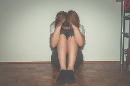 Depressed and lonely girl abused as young sitting alone in her room on the floor feeling miserable and anxiety cry over her life, dark image