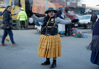 Elizabeth Acho, a municipal guard, directs the vehicular traffic in El Alto