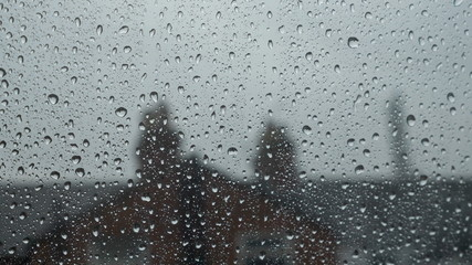 Large rain drops strike a window pane during heavy shower in England