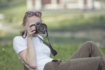 Girl with camera sits on a hill and photography