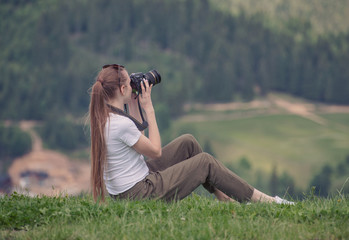 Girl with camera sits on a hill and photography nature. Summer day