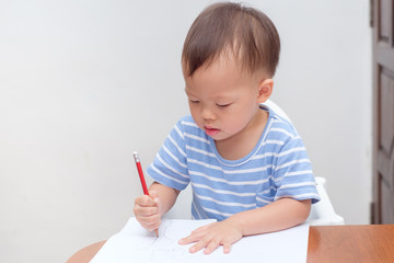 Cute Asian 2 years old toddler baby boy child writing / drawing with pencil, Preschooler doing homework, Creative play for toddler, Little kid prepare for kindergarten entrance exam, Shallow DOF