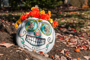 A day of the dead themed painted pumpkin sitting with fallen leaves on the ground.