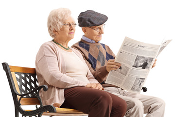 Seniors sitting on a bench and reading a newspaper
