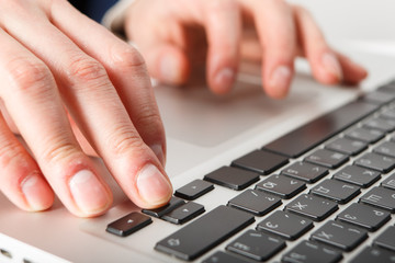 Close-up of hands businessman working at computer in office.