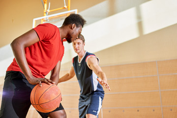 Young sportsman trying to interrupt black man dribbling ball while playing basketball in gym.