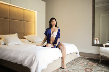 Charming woman sitting on her bed