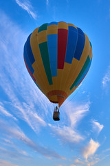 Colorful air balloon fly in the blue cloudy sky