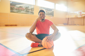 Handsome black basketball player with ball smiling and looking at camera while sitting on court floor in gym.