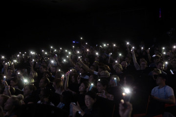 Attendees hold their mobile phone to shine light as part of the movement called #WomenCannes during a conference at the Cannes Lions International Festival of Creativity, in Cannes