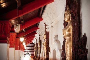 Old golden Buddha sculptures along the corridor at Wat Phra Mahathat Nakhon Si Thammarat, Thailand