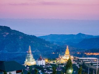 Phatchabun, Thailand on January 2018: summer travel concept from night and lighting turn on at Wat Prathat Phasornkaew temple and buddha statue during construction on mountain with blue sky background