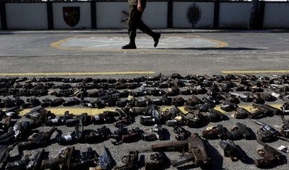A Brazilian  soldier walks past guns seized from criminals by the armed forces before being destroyed in Rio de Janeiro