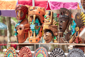 Stand with handmade, colorful Mexican souvenirs - figurines, traditional sculptures, Mayan calendars, masks