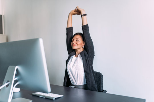 Break at work. Female office worker stretching hands.