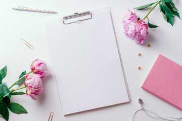 Feminine workspace with empty paper and pink peons on white background with copy space